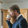 Photo of Michael Kutz drinking tea in a fine suit